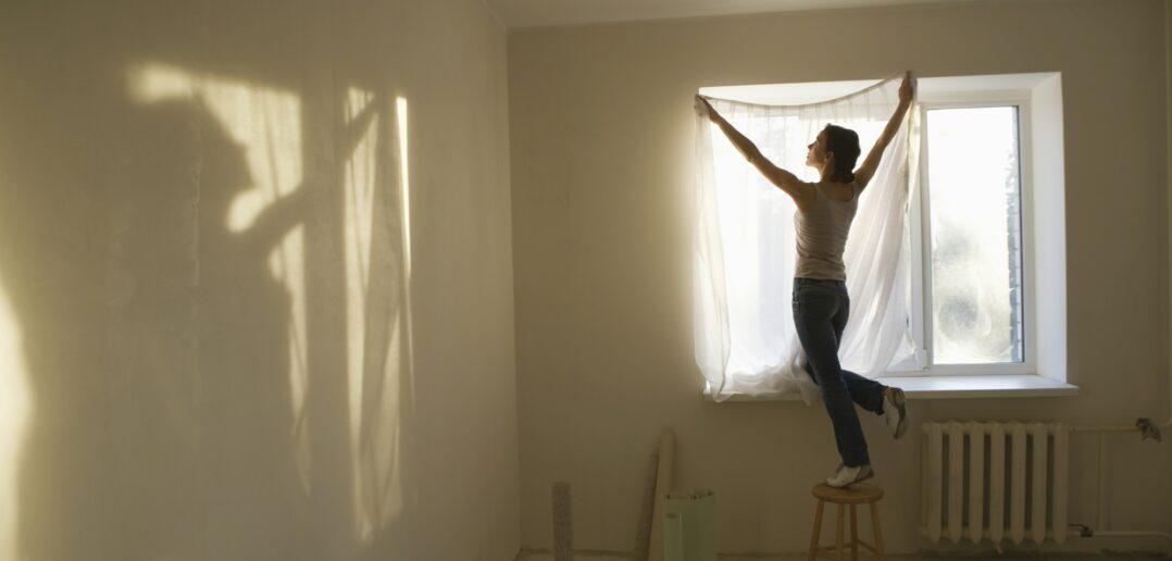 Kvinde sætter gardin på plads